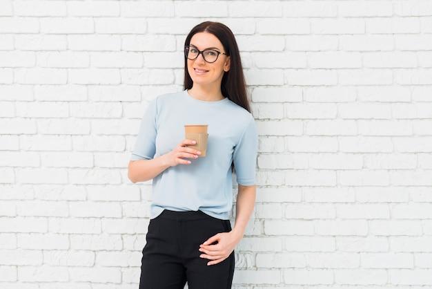 コーヒーカップと立っている若い女性
