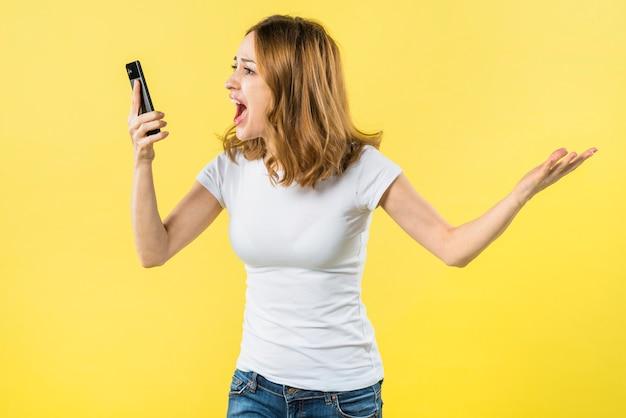 黄色の背景に対してスマートフォンで叫んでいる若い女性