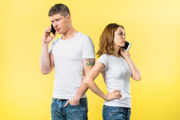 黄色の背景に携帯電話で話している若いカップルの背中合わせに立っています。