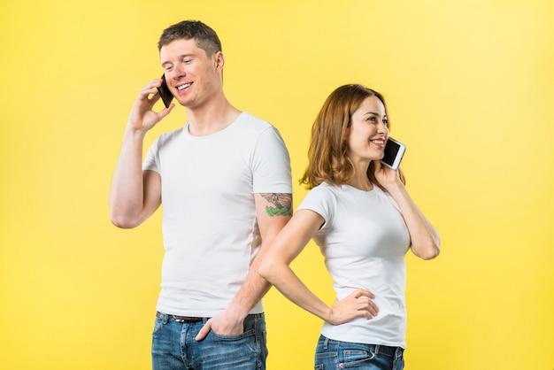 黄色の背景に立っている携帯電話で話している幸せな若いカップル