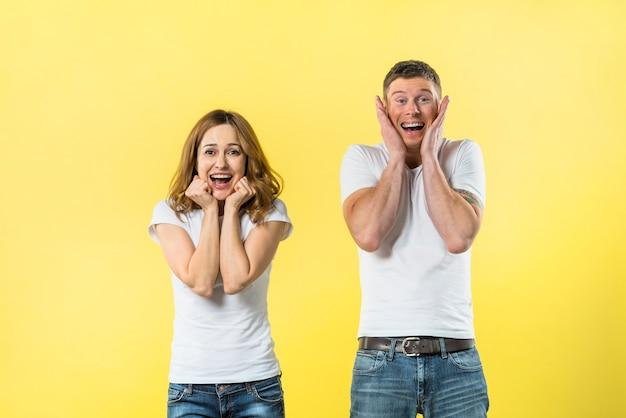 黄色の背景に対して興奮している若いカップルの肖像画