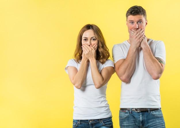 黄色の背景に彼らの口を覆っている若いカップルの肖像画