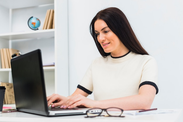 女性のオフィスでノートパソコンのキーボードで入力します。