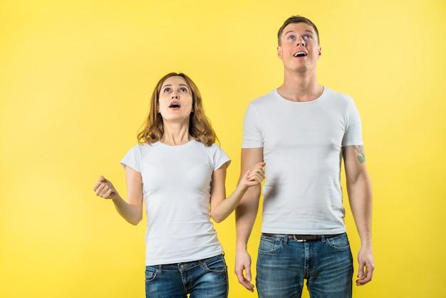 黄色の背景に対して見上げる若いカップル