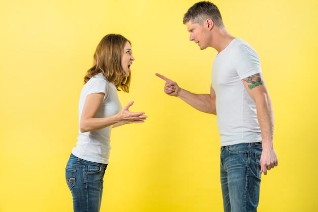 黄色の背景に対してお互いに主張して直面している若いカップルの立っている