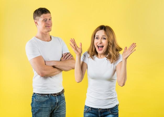 黄色の背景に対して驚いたガールフレンドの近くに立って満足している若い男