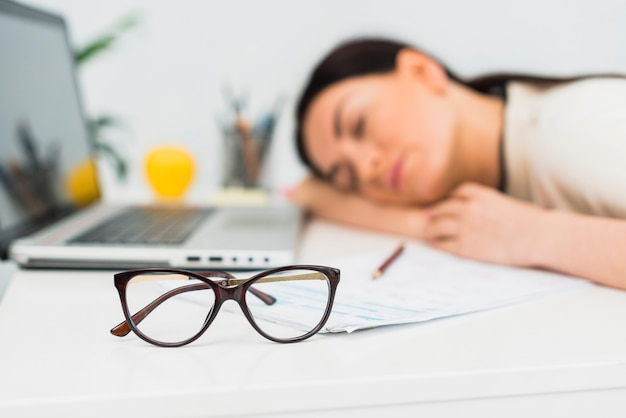 オフィスのテーブルで眠っている女性のメガネ
