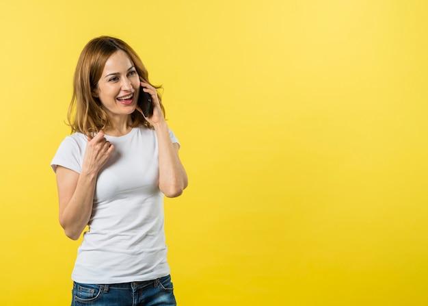 Счастливая молодая женщина разговаривает по мобильному телефону на желтом фоне