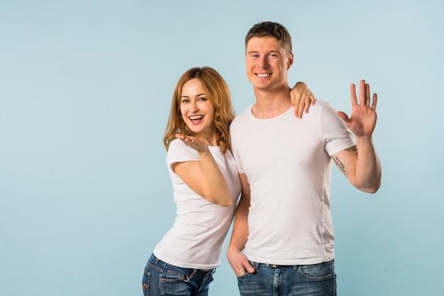 青い背景に対して手を振っている笑顔若いカップルの肖像画
