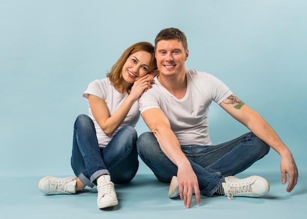 青い背景に対して床に座って笑顔の愛情のある若いカップルの肖像画