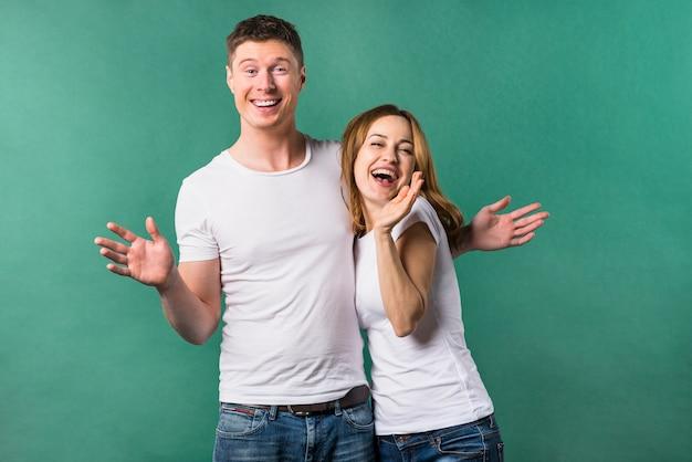 Портрет веселая молодая пара на зеленом фоне