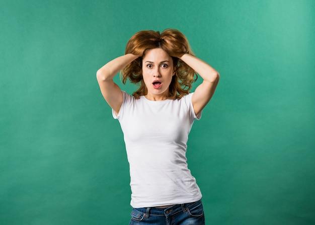 Портрет потрясен молодой женщины с ее руки в волосы на зеленом фоне