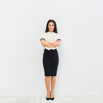 組んだ腕と立っている軽い服の深刻な女性