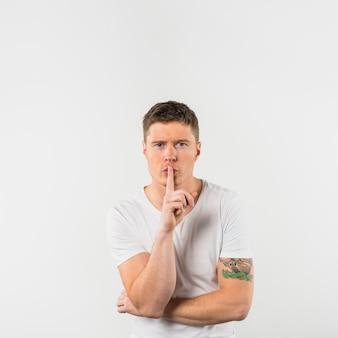 白い背景で隔離の沈黙のジェスチャーを作る若い男の肖像