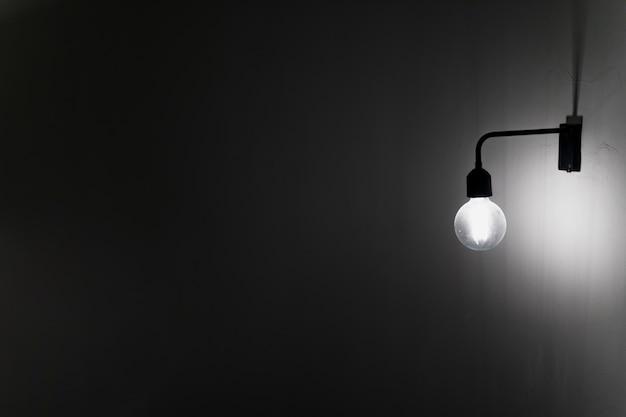 暗闇の中でコンクリートの壁に古い電球