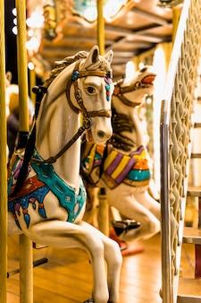 遊園地でカルーセルに乗る馬のクローズアップ