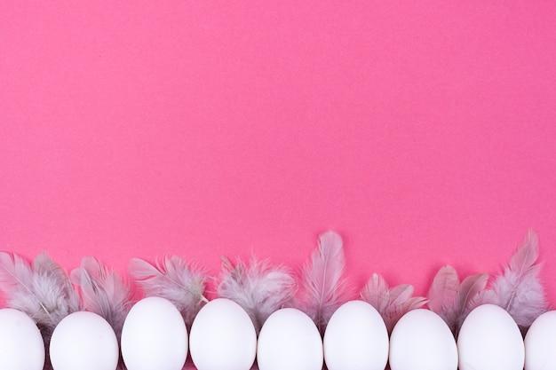 Ряд белых куриных яиц с перьями