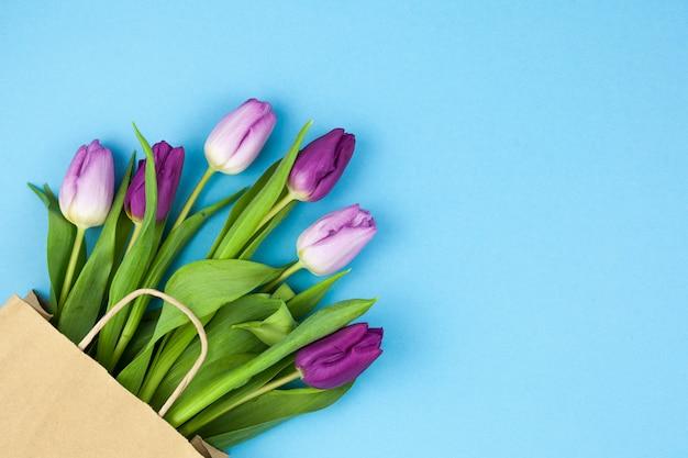 青い背景のコーナーに配置された茶色の紙袋と紫色のチューリップを束します。