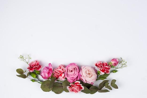 ピンクのバラと白の背景に赤いカーネーションの花のクローズアップ