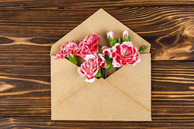 木製の机の上の赤いカーネーションの花と茶色の封筒