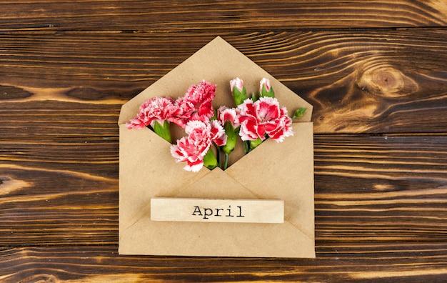 Апрельский текст на конверте с красными цветами на столе