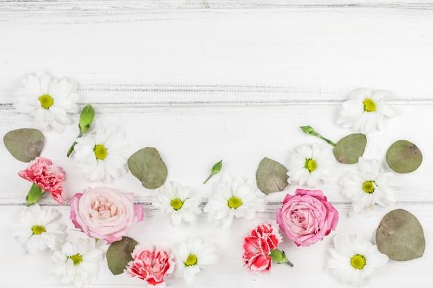 白い木製の机の上の美しい新鮮な花の様々な