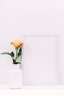 白い空白のフレームと木製のテーブルに新鮮なバラ