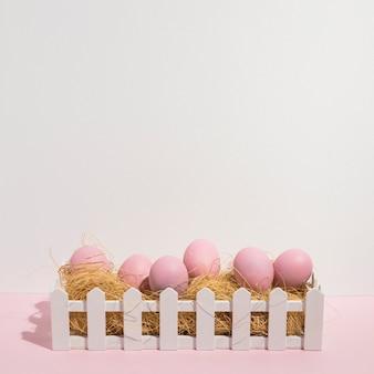 テーブルの上の干し草にピンクのイースターエッグ