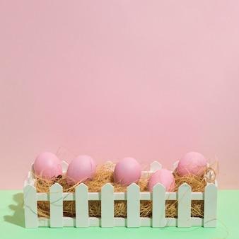 緑のテーブルの干し草にピンクのイースターエッグ