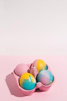 Разноцветные пасхальные яйца в небольшой подставке на розовом состоянии