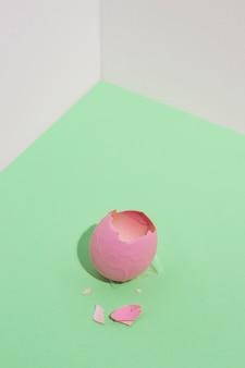 Разбитое розовое пасхальное яйцо на зеленом столе