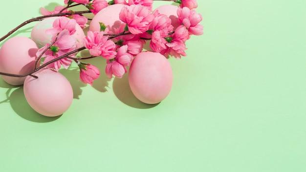 緑のテーブルの上に花とカラフルなイースターエッグ