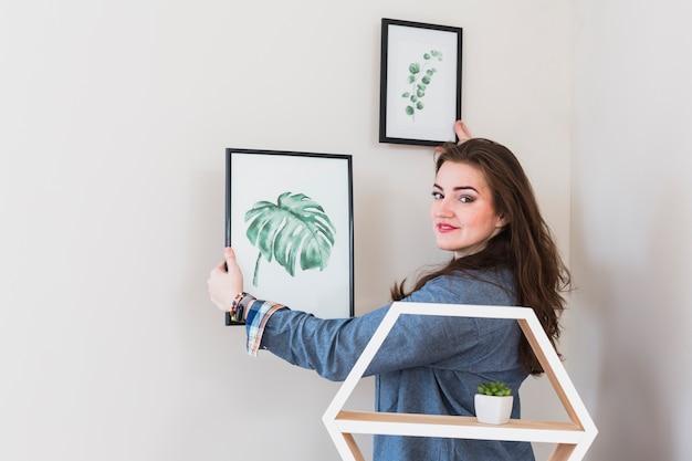カメラを探している壁に額縁を修正する若い女性の肖像画