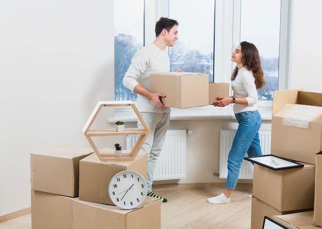 若いカップルが自宅で動く段ボール箱を開梱するお互いを見て