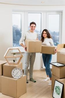 彼らの新しい家で手に段ボール箱を運ぶ若いカップルを笑顔の肖像画