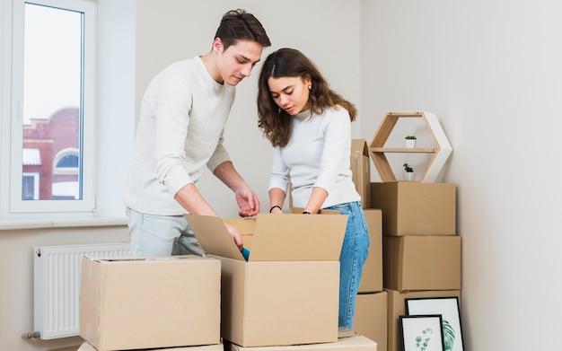 若いカップルが彼らの新しい家で段ボール箱を開梱