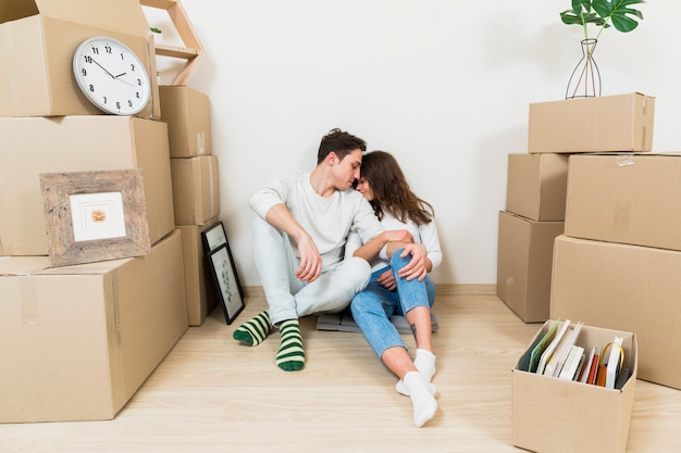 彼らの新しいアパートで段ボール箱のスタックの間に座っている若いカップルを愛する