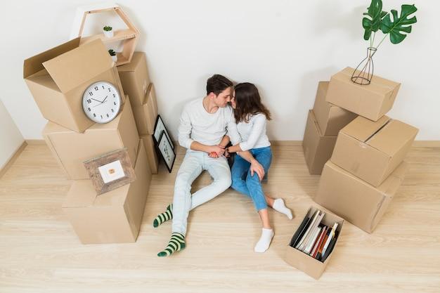 若いカップルが彼らの新しい家で段ボール箱に座ってお互いにキスの俯瞰
