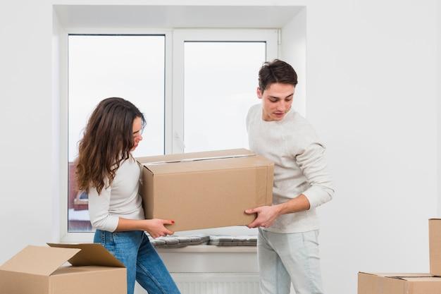 若いカップルが新しい家で大きな段ボール箱を運ぶ