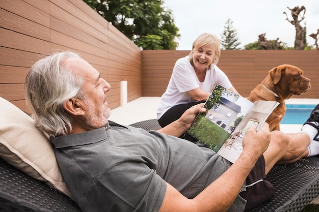 Пожилая пара с собакой в саду