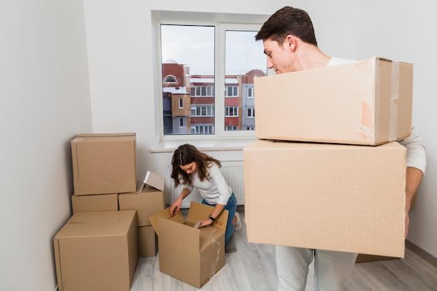 Мужчина несет картонные коробки, глядя на свою подругу, распаковывая коробку в новом доме