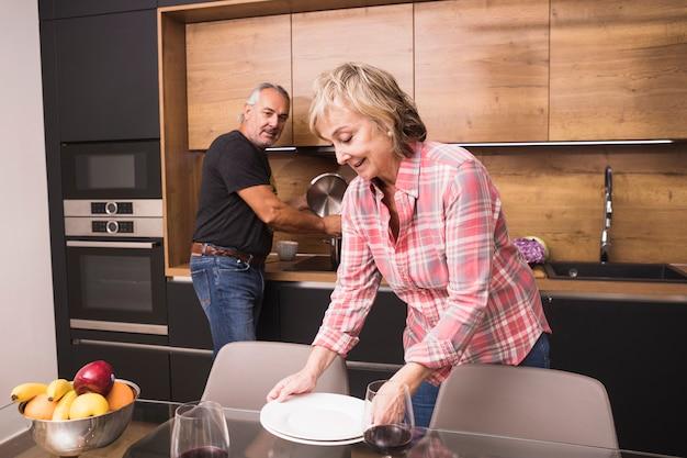 年配のカップルが台所で夕食を準備します。