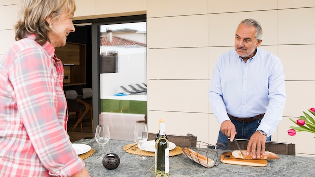 Пожилые супружеские пары, имеющие завтрак в саду
