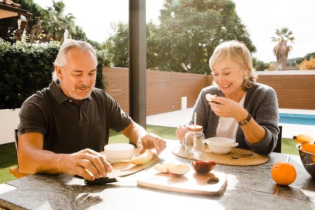 年配のカップルが庭で朝食をとって