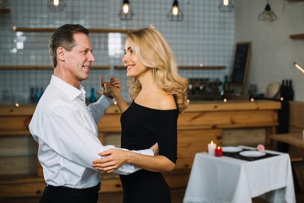 ロマンチックな夕食時に踊る夫婦