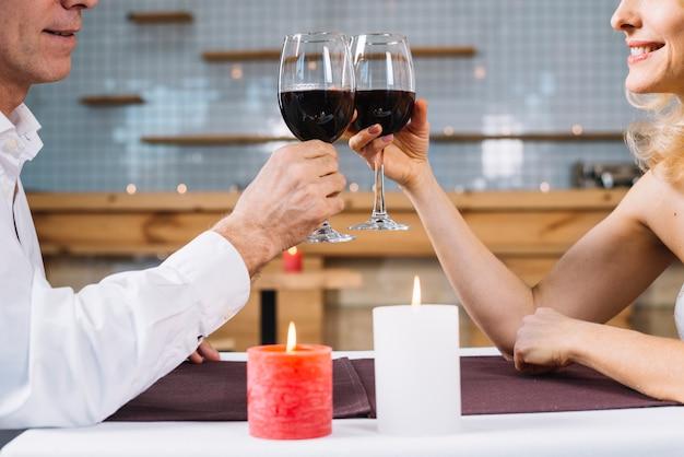 カップルが夕食時に乾杯の側面図