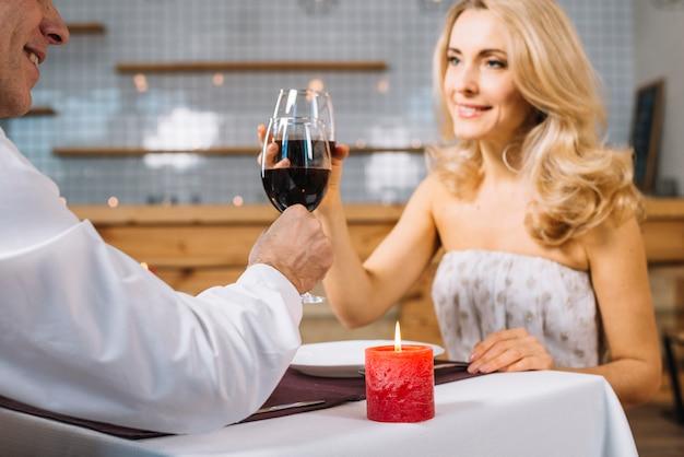 Средний снимок пары, пьющей вино
