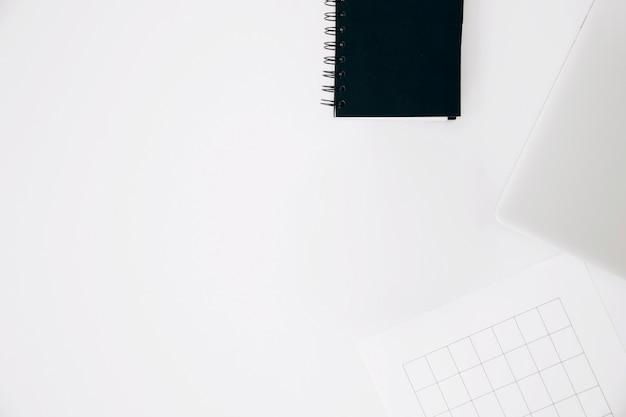 スパイラルメモ帳。ノートパソコンと白い背景で隔離のページ