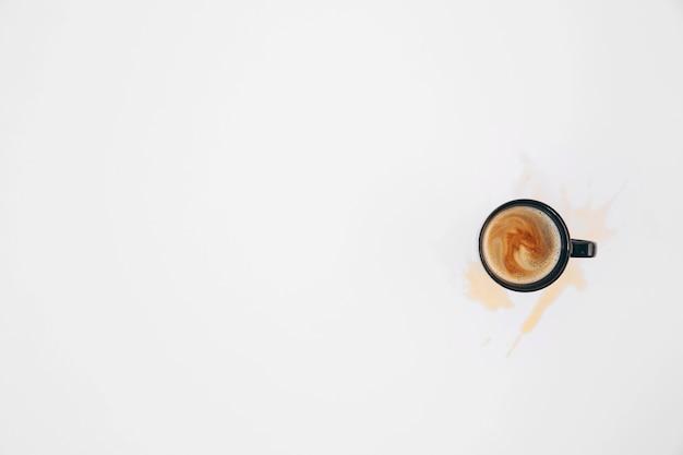 白い背景の上のマグカップからこぼれたコーヒー