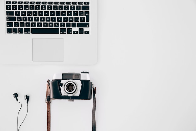 ビンテージカメラ。イヤホンと白い背景の上の開いているノートパソコン